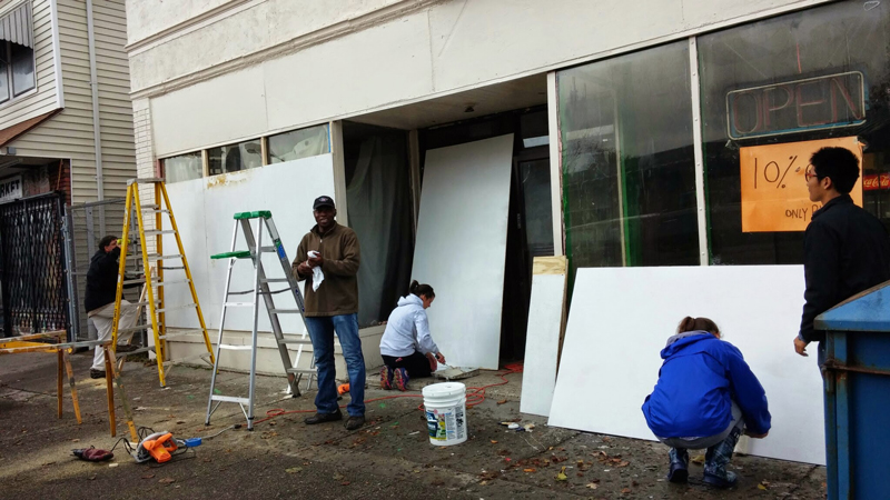 Ibrahim CIsse, President of the Bailey Avenue Business Association works alongside Mickey Vertino, President of the University Heights Collaborative and UB Honors Students to board up a building on Bailey Ave and prep it for public art.